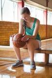 Mujer sonriente que lleva a cabo baloncesto mientras que se sienta en banco Fotografía de archivo