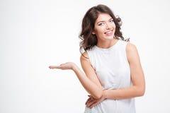 Mujer sonriente que lleva a cabo el copyspace en la palma Imagen de archivo libre de regalías