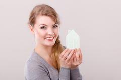 Mujer sonriente que lleva a cabo el modelo de la casa Imagenes de archivo