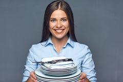 Mujer sonriente que lleva a cabo el sistema blanco de la loza foto de archivo libre de regalías
