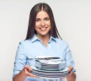 Mujer sonriente que lleva a cabo el sistema blanco de la loza imagen de archivo