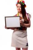 Mujer sonriente que lleva a cabo el tablero blanco de la muestra en el traje nacional ucraniano Imagen de archivo