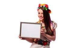 Mujer sonriente que lleva a cabo el tablero blanco de la muestra en el traje nacional ucraniano Fotos de archivo libres de regalías