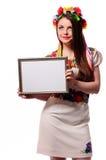 Mujer sonriente que lleva a cabo el tablero blanco de la muestra en el traje nacional ucraniano Fotografía de archivo