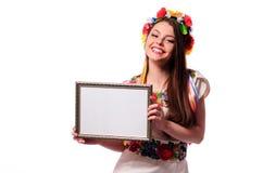 Mujer sonriente que lleva a cabo el tablero blanco de la muestra en el traje nacional ucraniano Fotos de archivo
