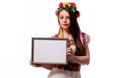 Mujer sonriente que lleva a cabo el tablero blanco de la muestra en el traje nacional ucraniano Foto de archivo