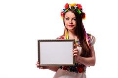 Mujer sonriente que lleva a cabo el tablero blanco de la muestra en el traje nacional ucraniano Imagenes de archivo