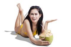 Mujer sonriente que lleva a cabo la bebida del coco Imagen de archivo libre de regalías