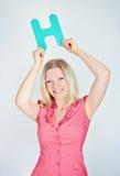 Mujer sonriente que lleva a cabo la letra H Imagen de archivo libre de regalías