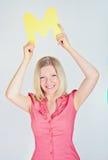 Mujer sonriente que lleva a cabo la letra M Fotos de archivo libres de regalías