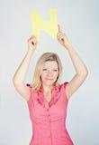 Mujer sonriente que lleva a cabo la letra N Imágenes de archivo libres de regalías