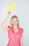 Mujer sonriente que lleva a cabo la letra P Fotografía de archivo libre de regalías