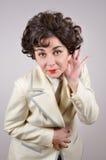 Mujer sonriente que lleva a cabo la mano detrás del oído Fotos de archivo