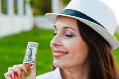 Mujer sonriente que lleva a cabo un dólar plegable Fotos de archivo libres de regalías