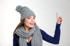 Mujer sonriente que lleva en la bufanda y el sombrero que destacan el finger Imagen de archivo libre de regalías