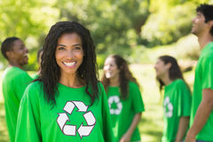 Mujer sonriente que lleva la camiseta de reciclaje verde en parque Foto de archivo libre de regalías