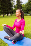 Mujer sonriente que medita sentarse en la estera al aire libre Imagen de archivo