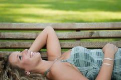 Mujer sonriente que miente en banco afuera Fotos de archivo libres de regalías