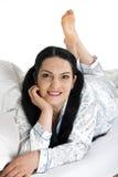 Mujer sonriente que miente en cama Imágenes de archivo libres de regalías