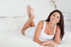 Mujer sonriente que miente en cama con las piernas cruzadas Fotografía de archivo libre de regalías
