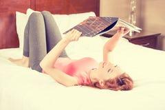 Mujer sonriente que miente en cama mientras que lee una revista, guía del viaje foto de archivo