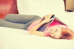 Mujer sonriente que miente en cama mientras que lee una revista, guía del viaje fotografía de archivo libre de regalías