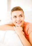 Mujer sonriente que miente en el sofá Fotos de archivo