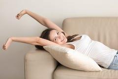 Mujer sonriente que miente en el sofá cómodo, mirando la cámara, str Fotografía de archivo