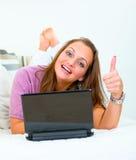 Mujer sonriente que miente en el sofá y que muestra los pulgares para arriba Imagen de archivo libre de regalías