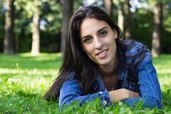 Mujer sonriente que miente en hierba Foto de archivo