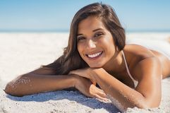 Mujer sonriente que miente en la arena Imágenes de archivo libres de regalías