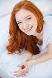 Mujer sonriente que miente en la cama en casa Imagen de archivo