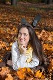 Mujer sonriente que miente en las hojas y disfrutar del otoño Imagen de archivo