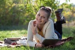 Mujer sonriente que miente en lecho con el ipad Imagen de archivo libre de regalías