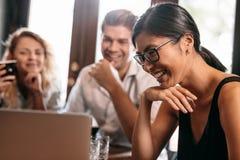 Mujer sonriente que mira el ordenador portátil con los amigos en café Foto de archivo