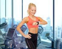Mujer sonriente que mira el reloj del ritmo cardíaco en gimnasio Foto de archivo