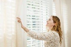 Mujer sonriente que mira hacia fuera la ventana Fotografía de archivo libre de regalías