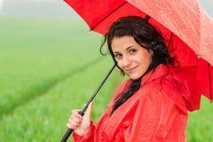 Mujer sonriente que mira la cámara durante la precipitación Fotografía de archivo libre de regalías