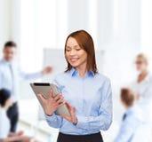Mujer sonriente que mira la PC de la tableta la oficina Fotografía de archivo libre de regalías