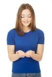 Mujer sonriente que muestra algo en las palmas Imágenes de archivo libres de regalías