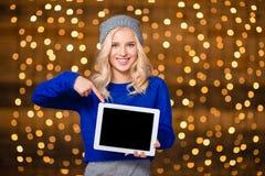 Mujer sonriente que muestra el finger en la pantalla de tableta en blanco Imágenes de archivo libres de regalías
