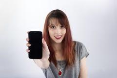 Mujer sonriente que muestra la pantalla de su teléfono Fotos de archivo
