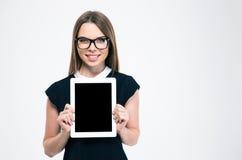 Mujer sonriente que muestra la pantalla de tableta en blanco Fotos de archivo