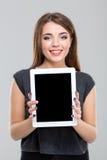 Mujer sonriente que muestra la pantalla de tableta en blanco Foto de archivo