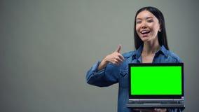 Mujer sonriente que muestra los pulgares-para arriba que sostienen el ordenador portátil verde de la pantalla, educación en línea almacen de video