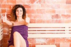 Mujer sonriente que muestra su pulgar para arriba mientras que se sienta en sauna Fotos de archivo