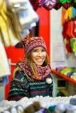 Mujer sonriente que negocia la ropa caliente en el mercado de la Navidad en Riga Fotos de archivo libres de regalías