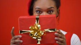 Mujer sonriente que oculta detrás del giftbox rojo, preparando el presente para St día de San Valentín metrajes