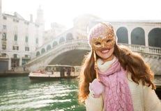 Mujer sonriente que oculta detrás de la máscara de Venecia cerca del puente de Rialto Imagen de archivo libre de regalías