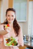 Mujer sonriente que ofrece un poco de ensalada Foto de archivo